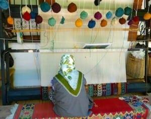 A weaver creates a carpet at Bulbul Mountain Looms.