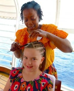 Grace Miller gets her hair braided by Janice Clark aboard the Disney Magic.