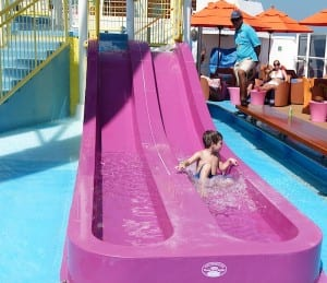 A water slide gets a workout under the watchful eye of a Carnival Breeze employee.
