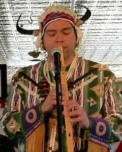 White Bull plays a Nez Perce flute during a visit aboard the S.S. Legacy.