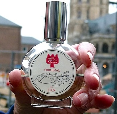 Tour guide Marion holds a bottle of Eau de Cologne in front of the place where it is made.