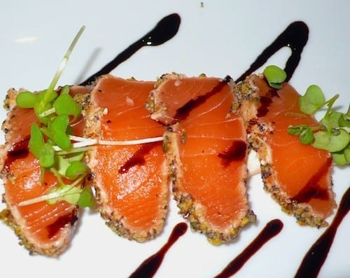 Appetizer of lemon pepper crusted salmon with chili sour cream