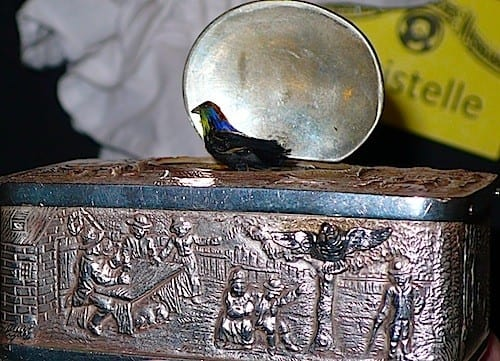 A teeny snuff box has a musical bird atop it.