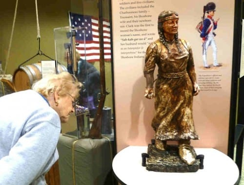 A cruiser from the American Empress inspects a statue of Sacajawea