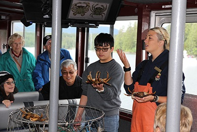 "Members of Noordam's ""Wildlife Cruise & Crab Feast"" excursion learn about trapping dungeness crabs prior to feasting on the tasty crabs at remote George Inlet Lodge, Ketchikan, AK."