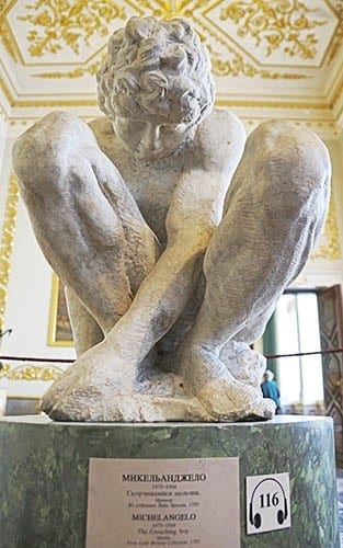 """""""The Crouching Boy"""" sculpture by Michelangelo, Large Hermitage building of The State Hermitage Museum."""