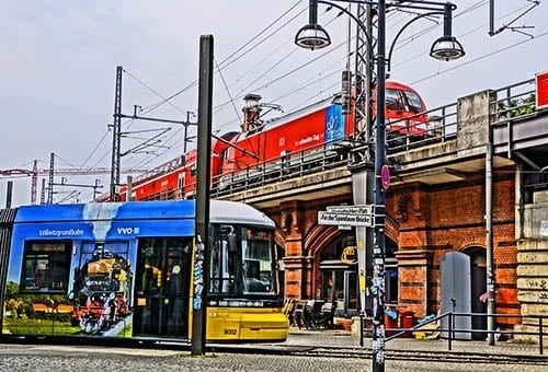 Colorful S-bahn train and a street tram passing at a Berlin transportation hub.