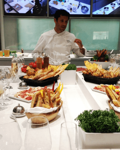 Chef Anthony Mauboussin prepares dinner with passengers in the Chef's Kitchen of Viking Ocean's Viking Star