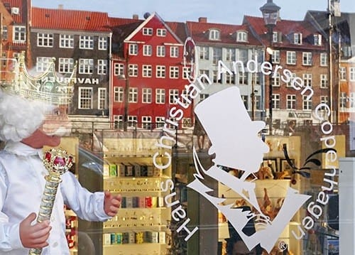 Nyhavn buildings reflecting in window of shop named for Hans Christian Andersen.