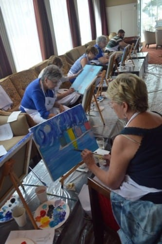 Passengers/art students work on their Honfleur harbor scene in art class aboard AMALegro