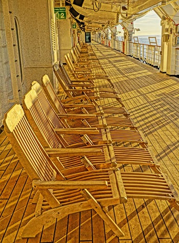 Deck chairs on Promenade deck at sunset.