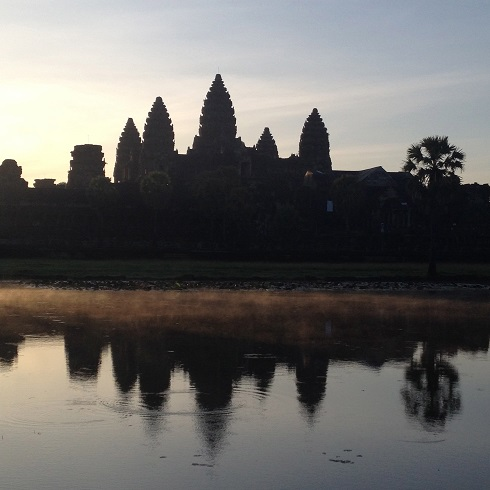 Morning mist rises from the lake that reflects Angkor Wat.