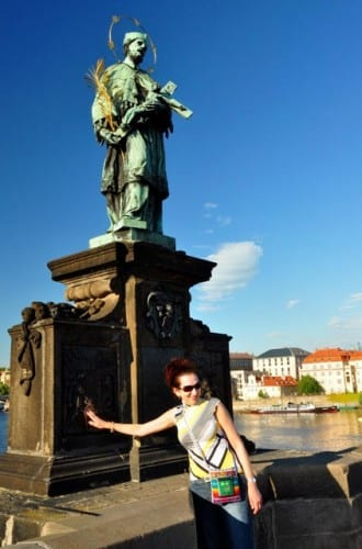 Visitors on Prague's Charles Bridge stop to touch the base of the statue of St. John Nepomuk who was martyred when he was thrown from the bridge.