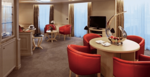 Living and dining areas in the Grand Suite of Silversea's Silver Spirit. The bedroom, bathroom with big tub, and walk-in closet are off to the left