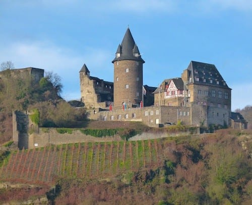 Harvested vineyards can be seen on the hillsides below historic castles on the Rhine.