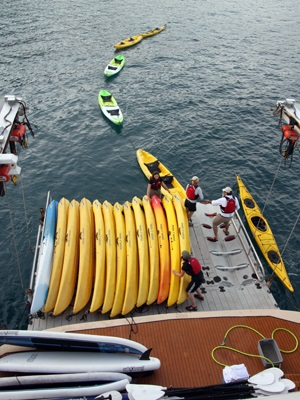 The crew unloads kayaks from the swim step on the stern of the ship.