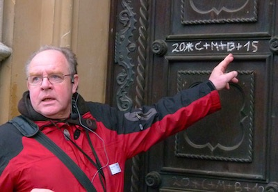 Tour guide Heinz Gerd Reis explains what the chalk marks mean on St. Castor Basilica.