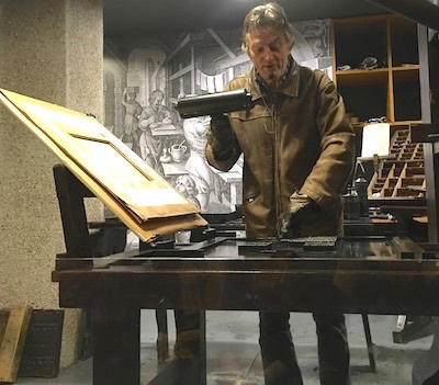 Tour guide Lothar Schilling demonstrates a replica of the Gutenberg printing press.
