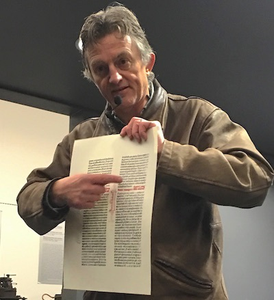 Tour guide Lothar Schilling shows a page of the Gutenberg Bible that he printed on a replica of the Gutenberg printing press.