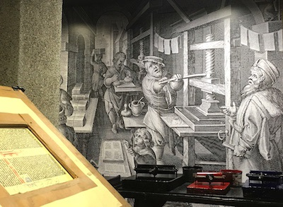 An exhibit allows visitors to see a replica of a Gutenberg printing press and other printing equipment.