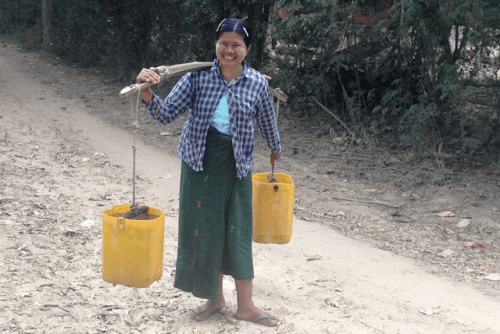 A woman carrying water home from the local well agreed to pose for a picture in Shwe Pyi Thar, a Myanmar town where most residents are involved in making candy from the sap of toddy palms