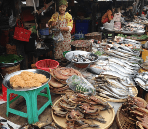 Pick out a fish and the lady will weigh it, then clean it at the market in Katha, Myanmar.
