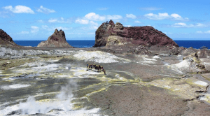 A tour group begins its walk at the tip of a volcano on White Island