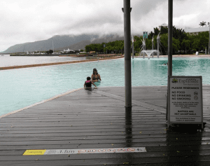 Cairns' downtown pool is next to the ocean, left, where crocodiles occasionally hide in the mud