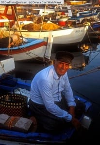 Turkish fisherman on his boat in morning in the old Roman harbor