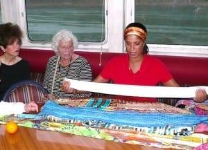Jenn McDaniel demonstrates scarf folding to Grande Caribe passengers.