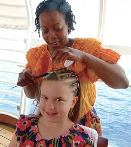 Grace Miller gets her hair braided by Janice Clark on a Disney cruise.