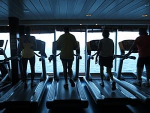 Passengers workout on the treadmills with a view of the South China Sea