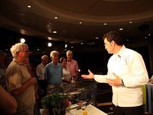 Executive Chef Alban Gjoka talks with passengers at cooking demonstratio