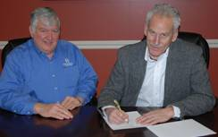 L-R: HMS Global Maritime In-House Legal Counsel Bob Herre and American Queen Steamboat Company Chairman and CEO John Waggoner sign documents for official handover of American Empress. (Photo courtesy of American Steamboat Company)