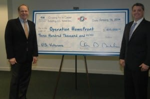 """Alan Buckelew presents a check for $300,000 to Jim Knotts, CEO of Operation Homefront, as a donation from Princess' """"Cruising for a Cause"""" sailing. (Photo courtesy of Princess Cruises)"""